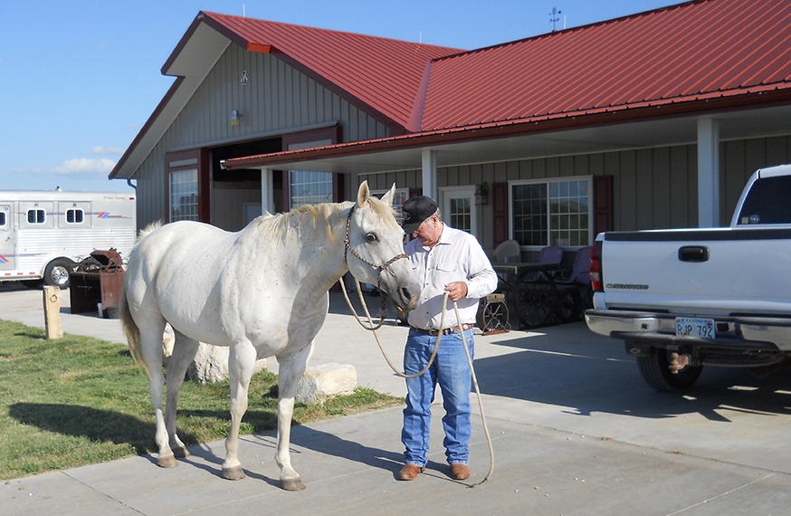 Renowned livestock nutritionist Dr. Phil Phar is with his horse, Flint, in front of the home-barn headquarters just north of Council Grove.