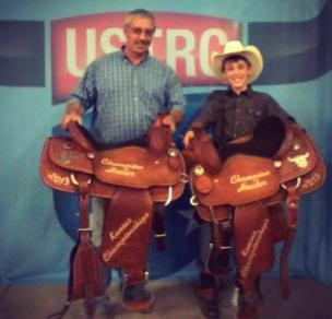 Camden Hoelting, right, Olpe, and his heeling partner, Bruce Grinstead, Rose Hill, showed their championship saddles they collected, along with $6,650, for roping and stretching four steers in 38.43 seconds, to win the No. 10 division at the United States Team Roping Championships in Hutchinson. by Frank J Buchman