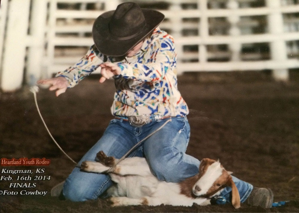 As all-around cowgirl, Michaela Peterson of Council Grove hands in the air completes her goat tying run during the February 16, 2014, Heartland Youth Rodeo Finals at Kingman. (Kent Kerschner Photography, fotocowboy.com)