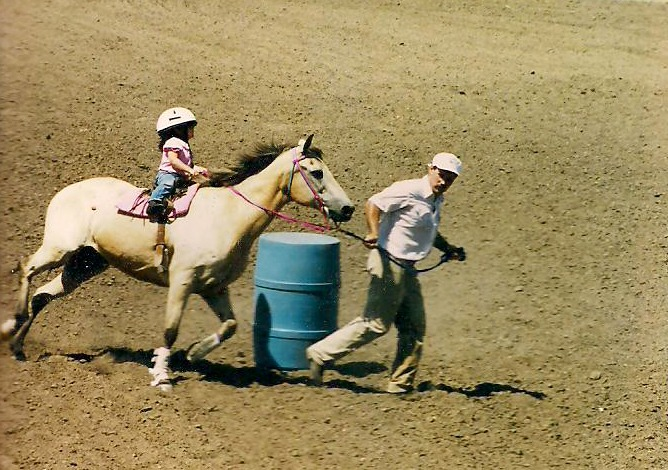 Competing almost before she could walk, Brooke Wallace is riding Lady as her dad, Mark, leads the way in six-and-under cloverleaf barrel racing at an Eastern Kansas Horseman's Association Show, when today's Junction City Rodeo Queen was just three-years-old.