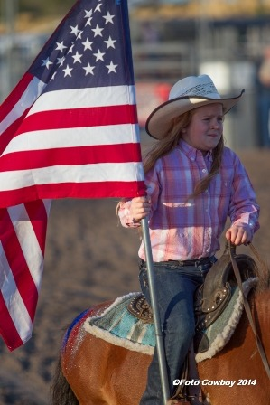 """Karlie Gibb, Strong City, daughter of Kyle and Jenna Gibb, and granddaughter of Kim and Lana Reyer, carried ole glory in the inspirational grand entry for the Flint Hills Bull Blowout at Strong City. (Photo by Kent Kerschner Photography """"Foto Cowboy."""")"""