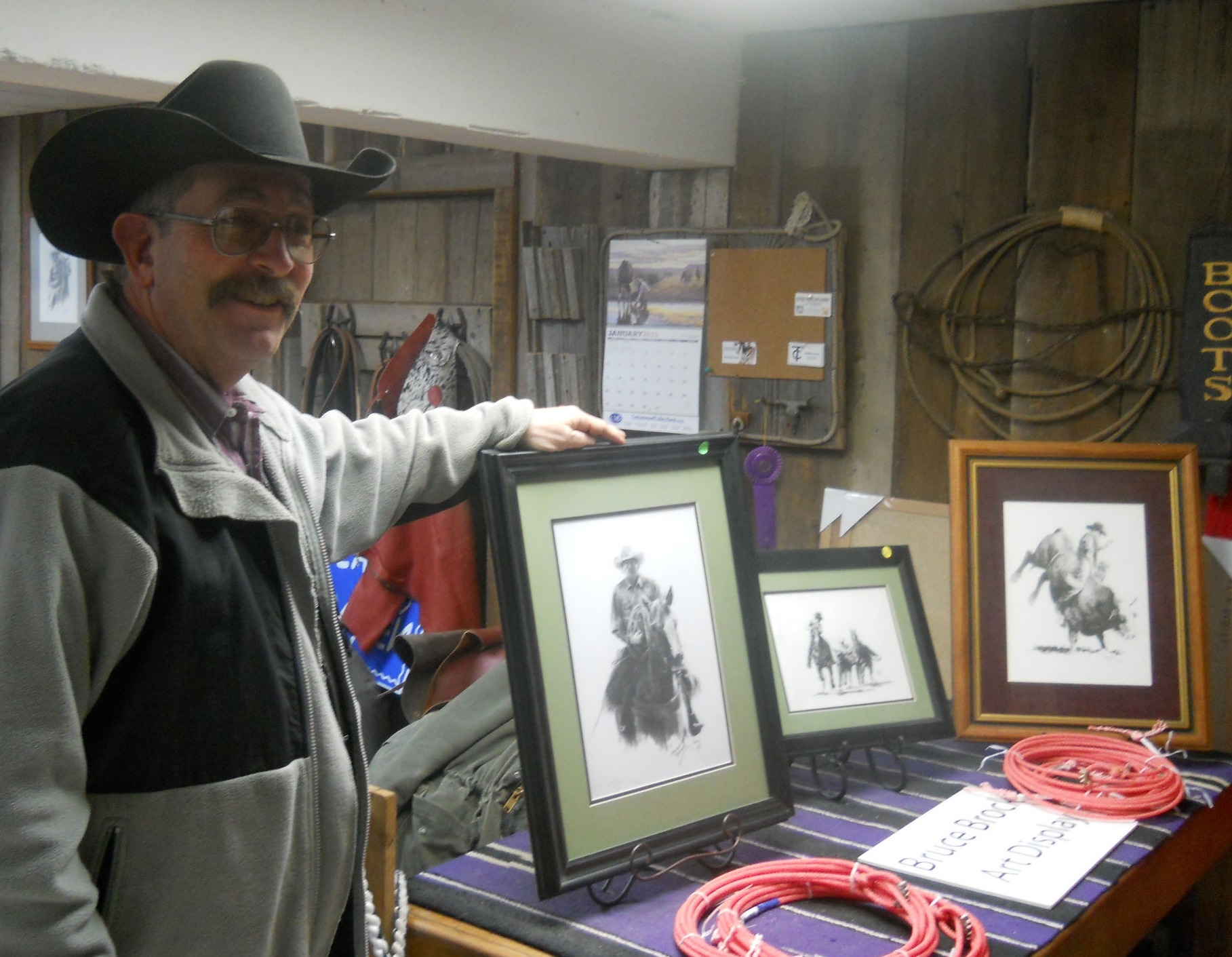 Leather craftsman-cowboy Bruce Brock is an artist, too, as verified by these elaborate pen-and-ink sketches, among the many diverse drawings and paintings he's done and has displayed in the lower level of Jim Bell and Son, Cottonwood Falls.