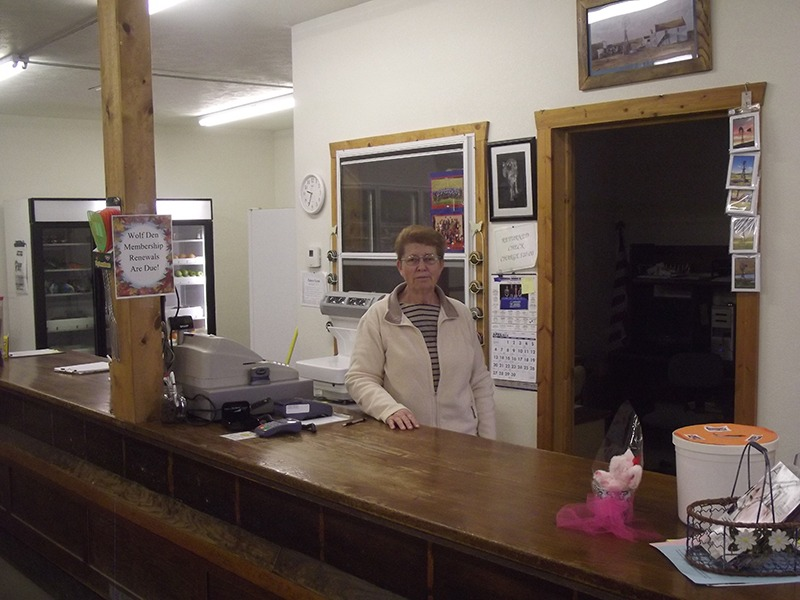 """Nida Gorwill is manager of the Wolf Den Market community cooperative grocery in Arthur, Nebraska, and serving all of Arthur County, the state's least populated county, and fringe counties as well. """"We get our groceries wholesale from Dredla's Grocery, owned by Steve and Debbie Clark in Hyannis, who get only a small markup on the merchandise,"""" Gorwill explained.  (Photo by Ron Jageler.)"""