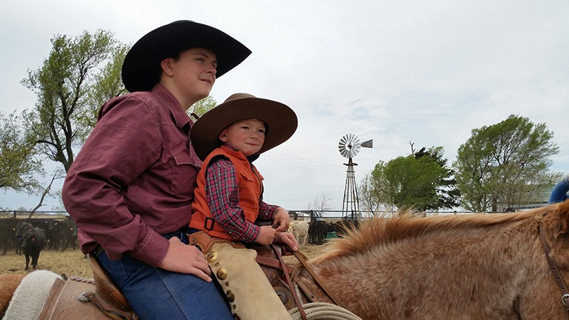 Now here's a cowboy team, Brayden Krepps with little brother Caleb on front during a spring ranch branding.