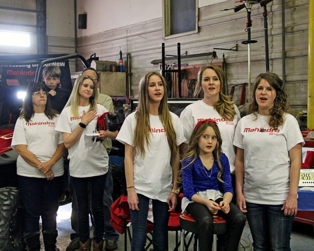 The Morris Singers presented a most inspirational rendition of the national anthem as part of the Military Appreciation Day at Heinen Repair Service, Valley Falls, before presentation of new Mahindra XTV to Army Lt. Col. Candy Smith winner of the Mahindra Tribute To The Brave Giveaway. Diane and Chantel Heinen pay tribute as Cierra, Cheyanne and Charity Morris, along with Ava Scallorn-Morris sing The Star Spangled Banner. (Photo courtesy of Lizzie Esparza, LE Photography.)