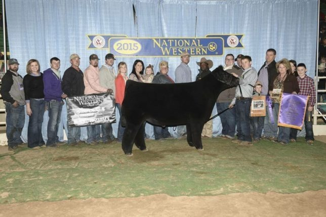 Andrew Hodges of Coffey County showed this champion at the National Western Livestock Show in Denver, and it was a happy occasion for Dylan Evans (just behind the winning exhibitor), wife Chelsea, the Hodges and Holmes families and many friends as all were smiles posing for the win picture.