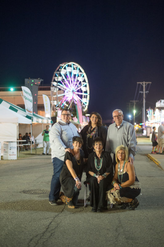 State Fair Time is family time and everybody gets involved when Dylan Evans of Lebo assists a large group of young people with their projects during competitions. But, there's still time to take in other fair festivities, as Dylan and his wife Chelsea, his parents John and Sara, and his sisters Megan and Kate pose for a family portrait among the Midway color and action.