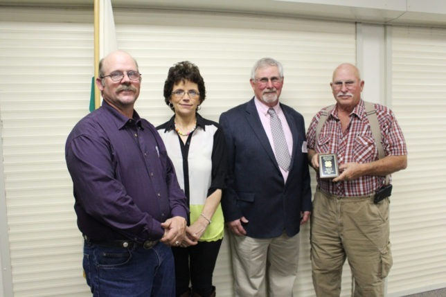 Larry Johnson, president of the Morris County 4-H Foundation, is with Charles H. (Chuck) Downes, right, accompanied by Charles R. and Cheryl Downes, left, after Chuck Downes was presented the Bronze Award during the annual banquet Friday evening. (Photo by Chelsea Richmond.)
