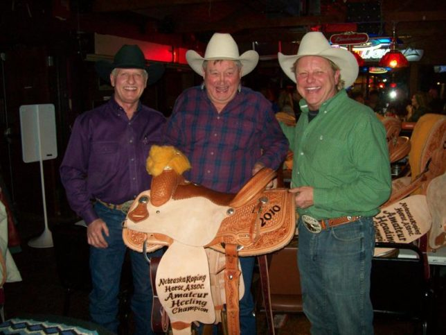 Bronco Billy Jim Hunter (center) was always biggest of smiles when presenting one of his custom made Bronco Billy trophy saddles as he is with champion amateur heeler Doc Lemmon and Zach Wiges, president Nebraska Roping Association.