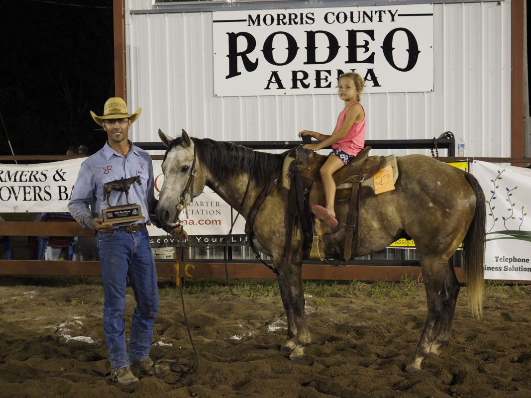 A trophy from the American Quarter Horse Association was presented to Adrian Vogel of Cottonwood Falls, representing the Robbins & Keith Ranches, for riding the Top Horse at the Santa Fe Trail Ranch Rodeo in Council Grove. Called Patch, the gray, five-year-old gelding registered as Four Chex Figure, owned by Dr. Tom Jensen and his wife Jan, of Blue Mound, is shown with Vogel's youngest daughter, Lola, six, mounted after winner's announcement at the Working Ranch Cowboys Association sanctioned competition. (Photo by Bruce Hogle.)