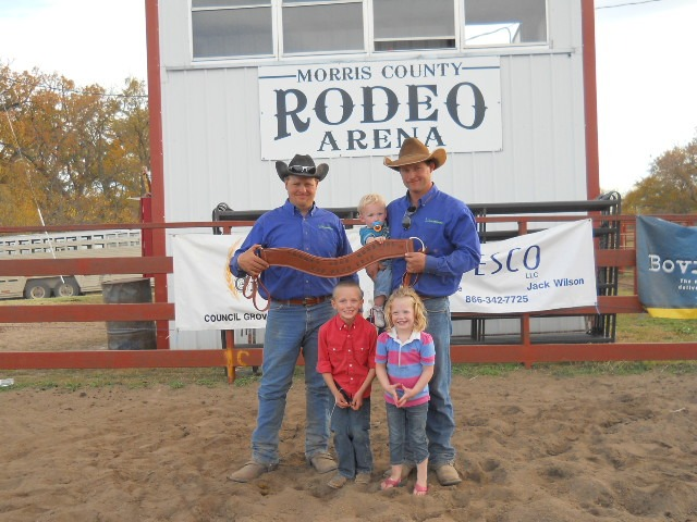 """Clint Bohnen of Alma received a breast collar signifying him """"Top Hand"""" at the Thomas K. Reed Memorial Ranch Rodeo in Council Grove. Jason Gibson of the Fallen Cowboy's Fellowship ramrodded the rodeo, and made the presentation with Bohnen's children, Trip and Charli, in the picture, along with Tucker Gibb."""