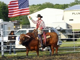 """Jason Dent, Humeston, Iowa, is better known as """"Whistle-Nut"""" to rodeo enthusiasts throughout the Midwest. Whistle-Nut and his bull, Oley, will be carrying ole glory in the grand entry, running the barrel race, doing other stunts and even posing with the kids for pictures and rides as a feature of the United Rodeo Association Finals, November 7-8-9, in Topeka. (Photo courtesy of Bob Fisher, TF Event Photography.)"""