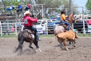 An all-around cowboy rides all-around horses as J.D. Draper of Oakley, honored as runner-up all-around cowboy in the Kansas High School Rodeo Association this year, shows championship form heeling for Nicole Sederstrom of Goodland, while riding his 11-year-old horse called Brandy, who's also used as a hazing horse in bulldogging.