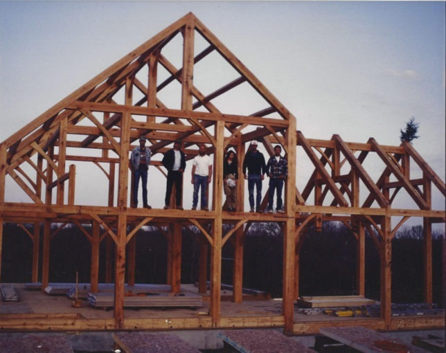 Construction crew posed with the completed post-and-beam interior for Brad Carter's two-level timber frame farm home near Paola.