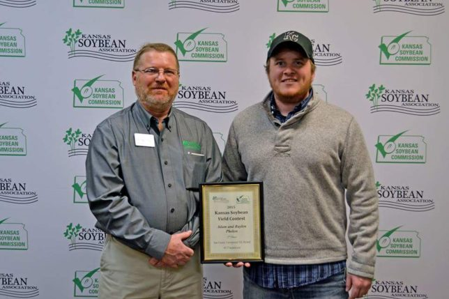 Proud dad-son farm partners Raylen and Adam Phelon of Phelon Farms at Melvern received the second place plaque in the east central district conventional till yield competition sponsored by the Kansas Soybean Association. (Photo from the Kansas Soybean Commission.)